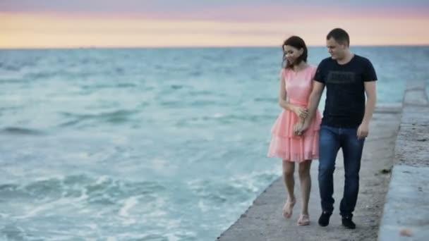 Mladý muž a žena jsou chůze na kamenný molo na moři převážně oblačno milenci