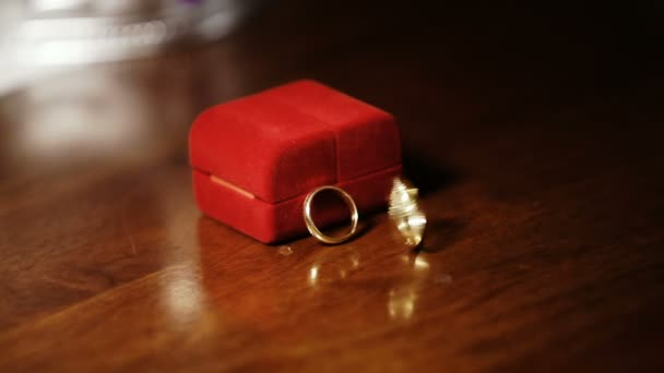 Static frame. Two gold rings swirl and spin On a wooden table near the red case Wedding