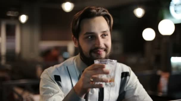 Brunette man sits alone in a bar and drinks whiskey. Smiling, happy, talking.