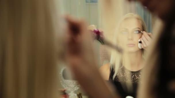 Kosmetický salón maskérka s štětec blond žena maluje stíny na oči