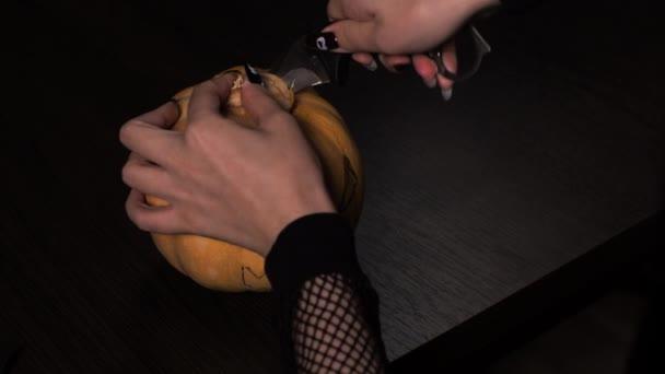 Mladá žena připravuje dýni na Halloween. Odřízne to vnitřek. Dovolená.
