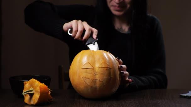 Mladá brunetka žena vyřezává dýni na Halloween Příprava na dovolenou