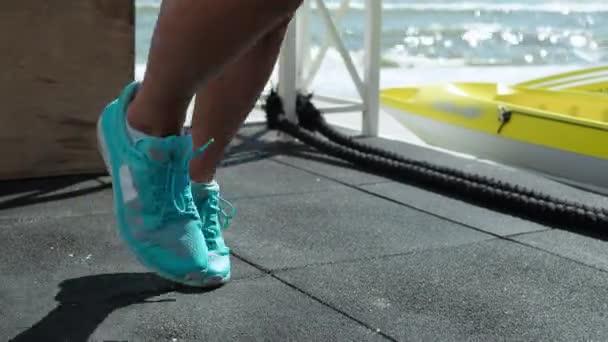 Blonde Frau trainiert Beine Laufen auf der Stelle Crossfit mit einem Trainer Am Strand Großaufnahme