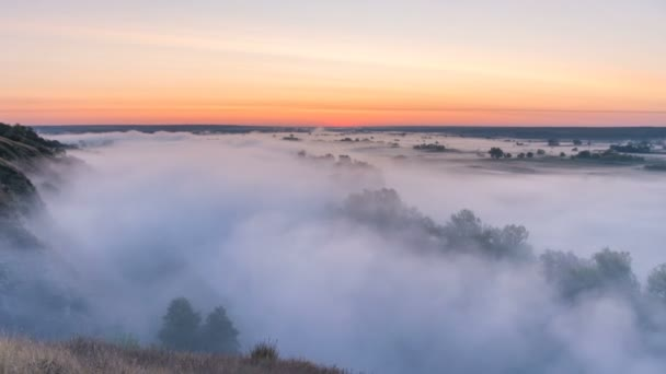 Timelapse mist curling over river and meadow on sunrise background