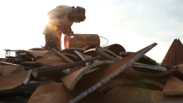 A man works at a construction site with a laser machine for cutting metal. Worker works on the background of metal scraps illuminated by the rays of the sun