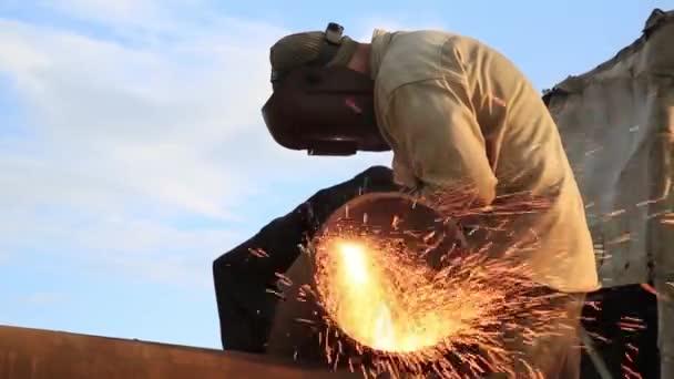Mužská ruka řeže kousky plynové trubky pomocí laserové řezací trubky. Řezání oceli sprejem jisker na staveništi. Jiskry při řezání