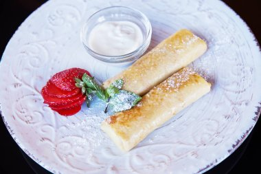 Pancakes with sour cream, strawberries close-up. Large plate of pancakes and stuffing. Tasty refresh yourself in morning