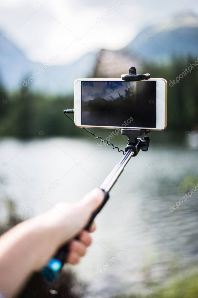 Beautiful photo on phone with selfie stick. Smartphone on selfie stick