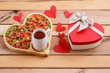 colorful dried fruits,tea and a heart-shaped gift on a wooden background