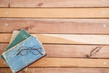 vintage books and vintage optical glasses on wooden background. the view from the top