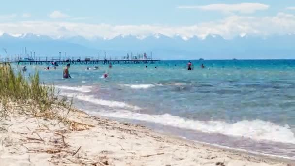 People are swimming on a sunny beach in a high mountain lake. Issyk Kul, Kyrgyzstan - August 2018.