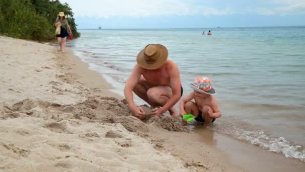 father with little son playing with sand on the beach