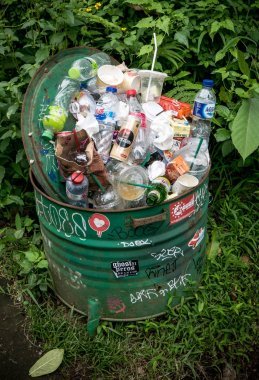 Bali, Indonesia - August 12th 2018: Trash bin full of garbage in Ubud, Bali - pollution is quite big problem in Bali