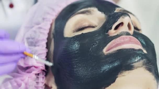 Kosmetikerin in lila Handschuhen setzt einer jungen Frau vorsichtig eine entschlackende schwarze Maske aufs Gesicht. Narbenpflege, Kosmetikerin trägt Gesichtsmaskencreme auf.