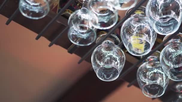 Prázdné čisté sklenice visí nad bar do racku. Mans ruky bere jeden křišťálového skla z kovovém podkladu. Detail