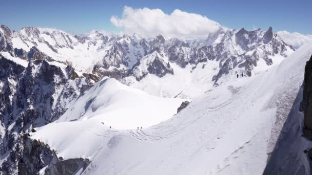 a group of climbers climbs the snow-capped peaks of the alpine mountains.
