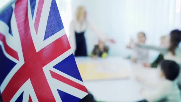 learning English in elementary school. Flag of Great Britain against the background of children with a teacher