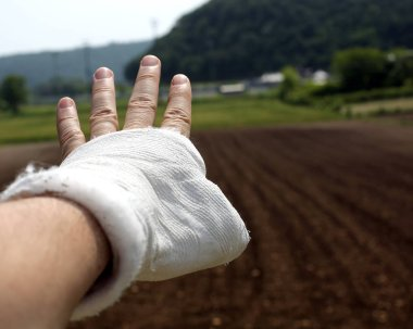 broken hand with white chalk outdoors in the countryside in a field
