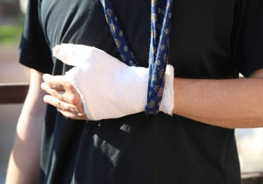 man after the incident with his arm around his neck and his hand fractured with the white cast and the black t-shirt