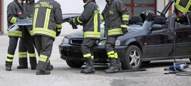 Vicenza, VI, Italy - May 10, 2018: Italian firefighters during a practice exercise with a broken car after the road accident