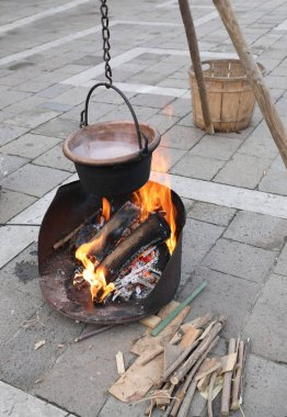 small camp during a reenactment with bonfires and an old copper pot filled with boiling water