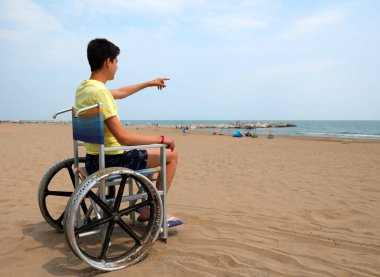 disabled boy on a wheelchair on the beach indicates the sea