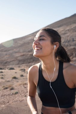 Woman standing in the desert with speakers in her ears and hold her head up as she laughs