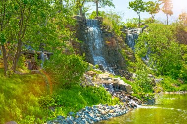 beautiful waterfall under sunlight, many beautiful water jets surrounded by green forests.