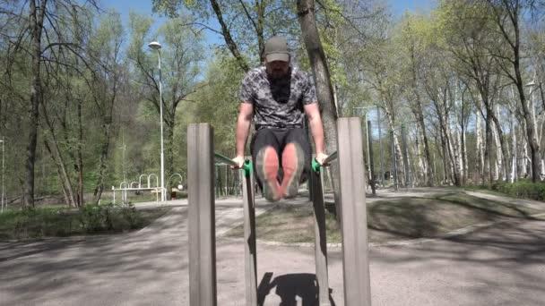 Der erwachsene Mann hebt die Beine am Lenker. Sportplatz. hohe Bäume im Park. Sommerzeit. sonniger Tag. 4k-Video