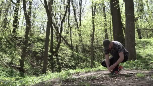 Az ember megáll az út. Visszatér a házba. A City Park. Szemben a nap. Nagy fa. Nyári idő. Süt a nap. 4k videóinak