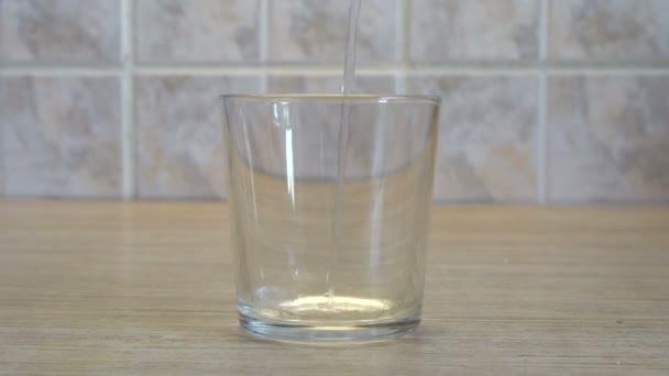 Transparentní sklo Cup. Voda se nalévá z výše. Interiér kuchyně. Světlé pozadí. Dřevěný stůl. Čtvercové dlaždice na zdi. Uhasit žízeň