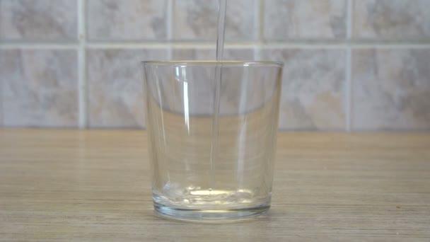 transparente Glasschale vorhanden. Wasser ergießt sich von oben. Kücheneinrichtung. heller Hintergrund. Holztisch. quadratische Fliesen an der Wand. Durstlöschung.