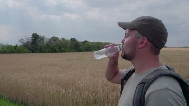 Traveler drinking water. Against ripe wheat field. The light of the day. Unshaven face. Dark baseball cap. Half-length portrait. Slow motion.