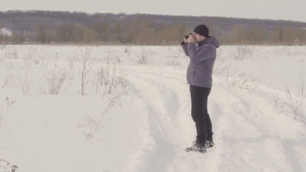 Egy ember veszi a képek terén. Téli szezonban. Meleg ruházat. Sok a hó. Teljes növekedés. Fényes nap. Nézd, hogy a derék. 4k videóinak
