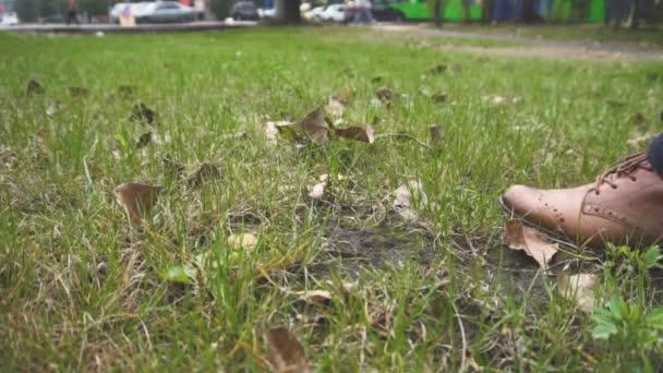 Nohy v kalhoty a kožené boty. Pomalé kroky. Zelená tráva. Městská krajina. Čas podzimu roku. Hrabanka. Bez tváře. Fragment z těla