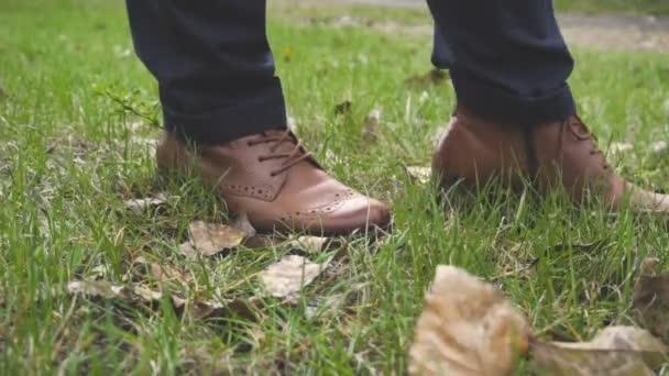 Kožené Dámské boty. Nohy a kalhoty. Podzimní počasí. Zelená tráva. Žluté listy. Brown. Detail nohy. Módní oblečení