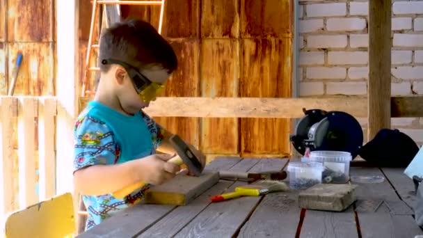 Ein kleiner Junge steckt sich einen Nagel. Holztisch. Landhaus. auf der Gesichtsschutzbrille. Werkzeugbank. Warme Jahreszeit.
