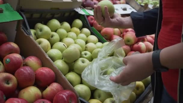 The girl in the big store. Chooses apples. Shop. Blue jacket on.