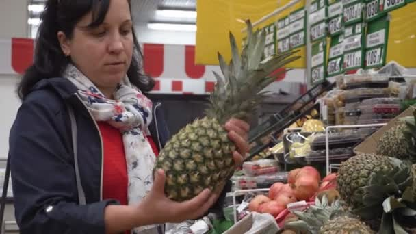 The girl in the big store. Selects the pineapple. Shop. The dark color of the hair. Blue jacket on.