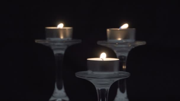 Burning candles on glass candlesticks. Dark background. Mystical atmosphere. Romanticism. Holiday. Sorrow. Death.