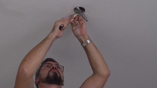Vousatý muž pracující s elektrické dráty. Povolání elektrikář. Bílý strop. Pohled zdola