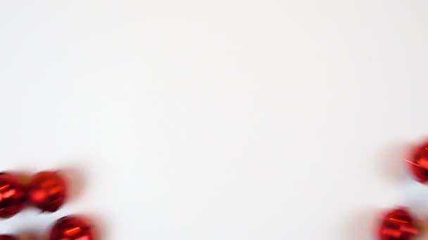 Červená kovová zvony. Symbolem svátku 14. února. Přejít na bílém pozadí. Zpomalený pohyb. Den svatého Valentýna, nový rok, Vánoce.