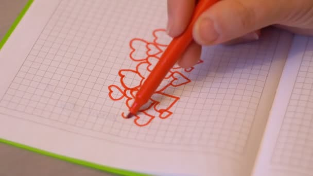 Female hand with a crayon draws hearts. A piece of notebook. Symbol of love. Valentines day. Design element. Feelings and emotions. 4K video