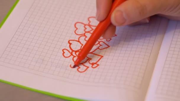 Ženská ruka s tužkou nakreslí srdce. Část poznámkového bloku. Symbol lásky. Den svatého Valentýna. Designový prvek. Pocity a emoce. 4k video