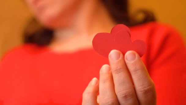 Dívka držící červené srdce papíru. Láska pro jinou osobu. Valentýna karty. Designový prvek. Pocity a emoce. 4k video