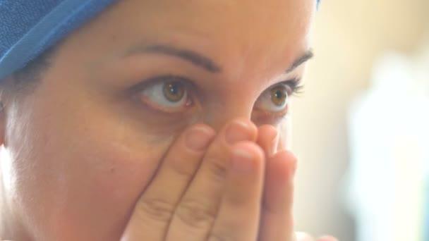 Mladá žena dá krém na její tvář. Masáže prsty. Kosmetická procedura. Přípravky proti stárnutí. Doma se o sebe starat. Zblízka. 4k video