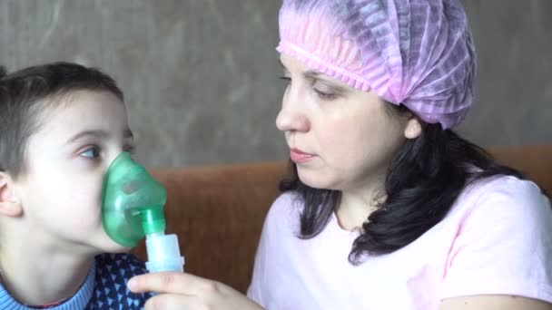 A young woman in a pink hat. A little boy makes inhalation. Room in the house. Human health. Nurse. 4K video