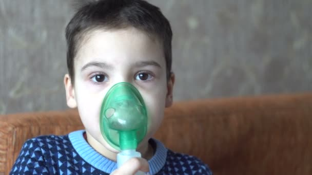 A little boy makes inhalation. Medical treatment. Disease. Room in the house. Human health. 4K video
