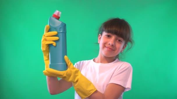 Mädchen in gelben Handschuhen. in den Händen des Waschmittels. Direkter Blick. Grüner Hintergrund. Teenager-Mädchen. dunkle Haare. dunkle Haut. die Form eines Mannes bis zur Taille. Weißes Hemd. 4k-Video.