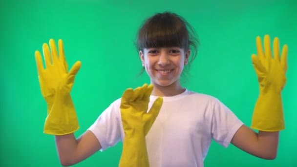 Girl in yellow gloves. Playing with hands. Green background. Teenage girl. Dark hair. Dark skin. The form of a man to the waist. White shirt. 4K video.
